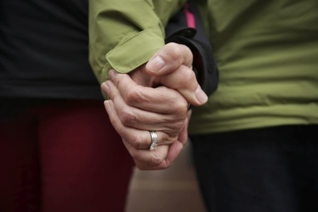 A close-up shot of a couple holding hands.