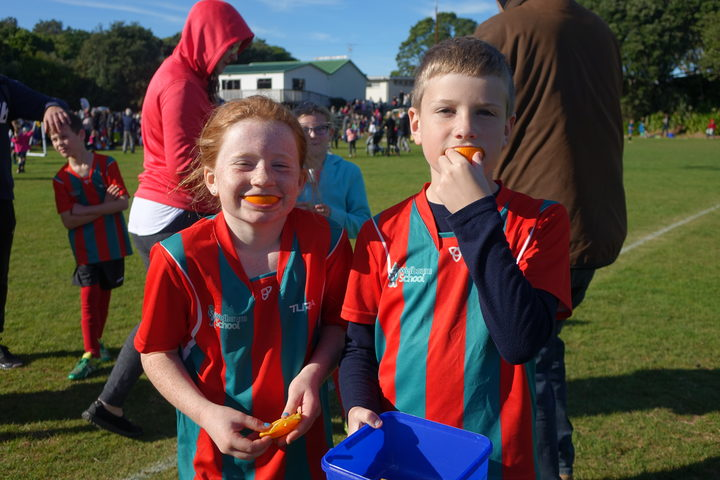 Siblings Jaimee, left, and Riley Seddon enjoy half-time oranges at the Central Football junior tournament at Peringa Park
