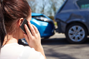 A woman makes a phone call, looking at a minor accident between two cars.