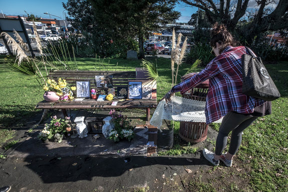 The daughter of homeless man Keith Johnson, who died here on July 1, wraps material around the rubbishbin in St Peter's cemetery in Onehunga where they have made a memorial.