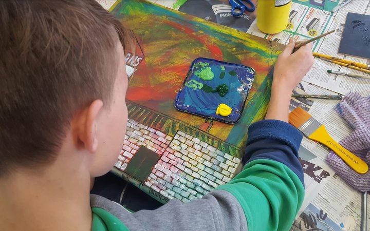A He Kākano student works on his art.