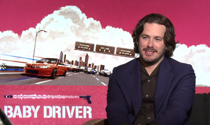 Edgar Wright in front of Baby Driver artwork