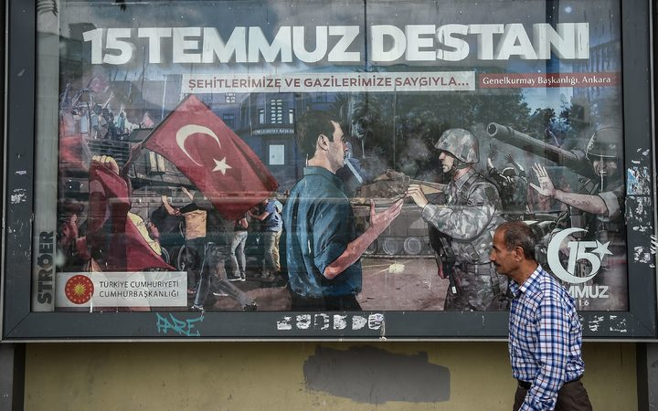 "A man walks past a giant billboard reading ""Legend of July 15"" for the anniversary of the last year's attempted coup in Turkey"