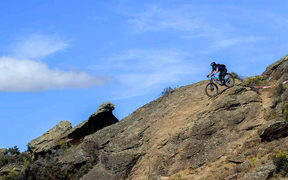 Bike and rider starting descent of rocky outcrop