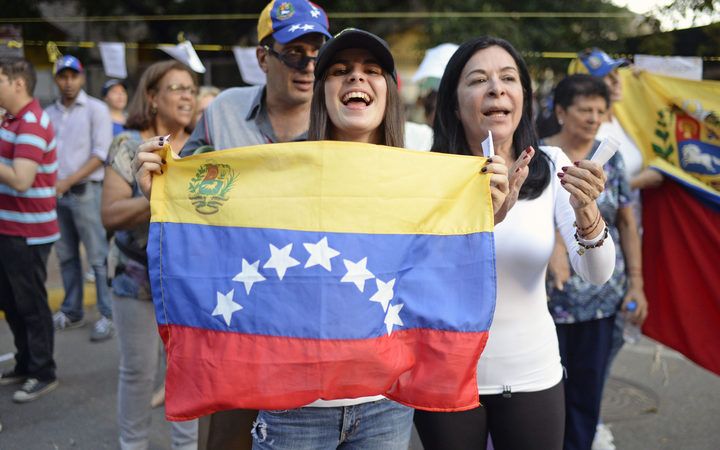 Opposition activists celebrate outside polling stations after taking part in an opposition-organized vote to measure public support for Venezuelan President Nicolas Maduro's plan to rewrite the constitution.
