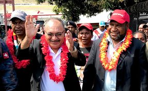 Papua New Guinea's prime minister Peter O'Neill  (with glasses) celebrates being declared winner of the election in his Ialibu-Pangia electorate, alongside fellow victorious People's National Congress member James Marape (red hat).