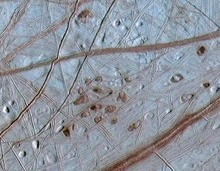 Reddish spots and shallow pits peppering the enigmatic ridged surface of Jupiter's moon Europa.