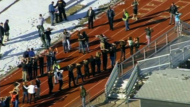 TV news footage shows students lining up to be checked by police at a running track.