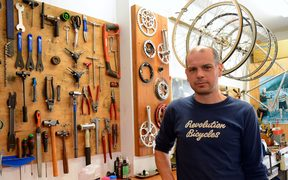 Owner in a bike shop surrounded by tools on board and hug up wheels