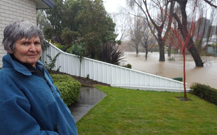 A worried Christine Bridgman returns after a night a way to check on her Riverlaw terrace home in Christchurch, but the street outside her house is fully flooded.