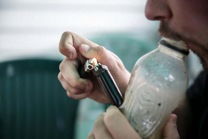 A male smoking using a homemade bong.