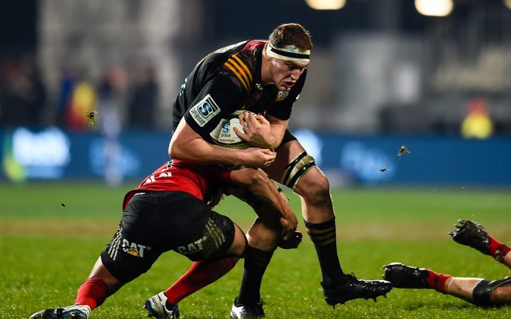 Brodie Retallick of the Chiefs is tackled by Crusader Richie Mo'unga.