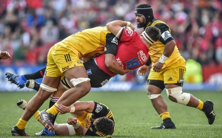 Sam Lousi, left, of the Hurricanes tackles Lourens Erasmus of the Lions during the Super Rugby semi-final match.