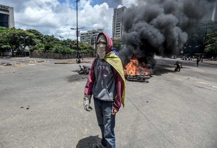 An anti-government activist stands in front of burning police bikes during a protest in Caracas against the elections for a Constituent Assembly.