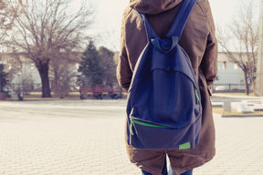 A photo of a teenager from behind showing her back pack and a school yard in the back ground
