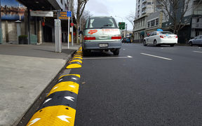 Speed bumps being used as barriers to prevent buses from hitting roadside obstacles.