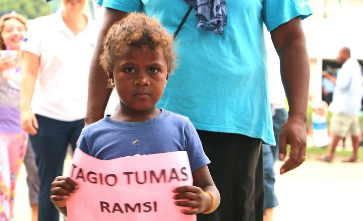 "A boy holds a sign saying ""Thank you very much RAMSI"""