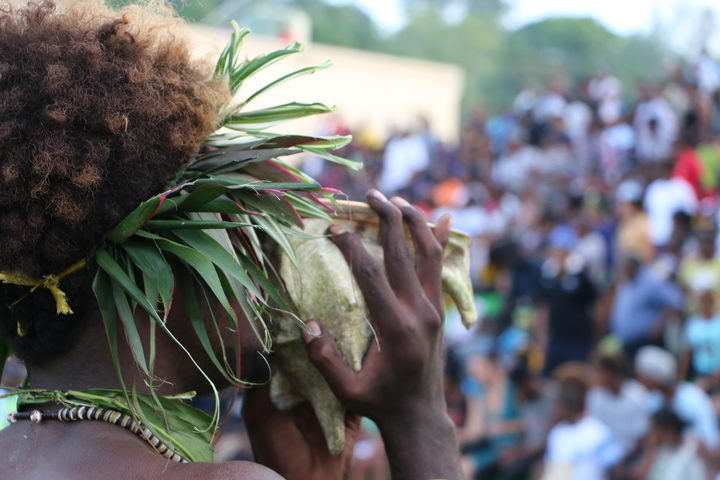 A Solomon Islands' cultural performer blows a conch shell to announce the arrival of Pacific leaders for the RAMSI farewell events. June 2017