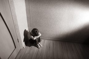 A young boy sits in the corner with his head in his hands (file photo)