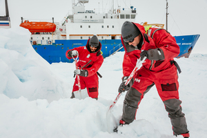 Passengers on the MV Akademik Shokalskiy prepare a surface for a helicopter landing