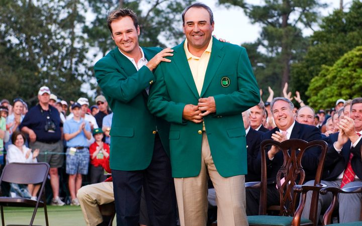 Angel Cabrera is presented with his green jacket by Trevor Immelman after winning the Masters in 2009.