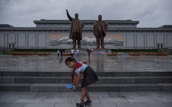 A young girl cleans steps as people bow before the statues of late North Korean leaders Kim Il-Sung and Kim Jong-Il in Pyongyang.