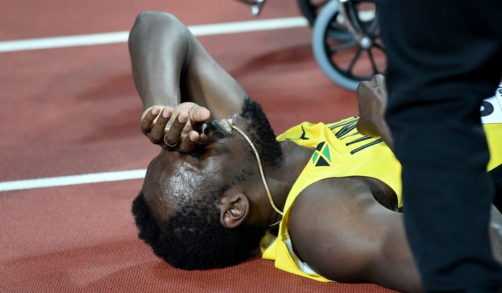 Usain Bolt lays on the track after pulling up injured in the final of the 4x100m relay.