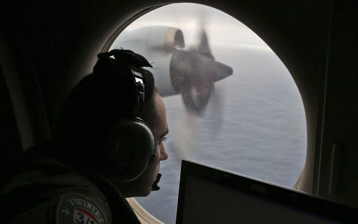 A crew member on a Royal Australian Air Force AP-3C Orion searches for missing Malaysia Airlines flight MH370 in the southern Indian Ocean in 2014.
