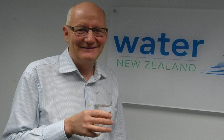 Man holds glass of water in front of  Water NZ sign