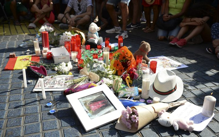 People sit next to flowers, messages, stuffed toys and others items displayed on Las Ramblas boulevard in tribute to the victims of the Barcelona attack, a day after a van drove into pedestrians.