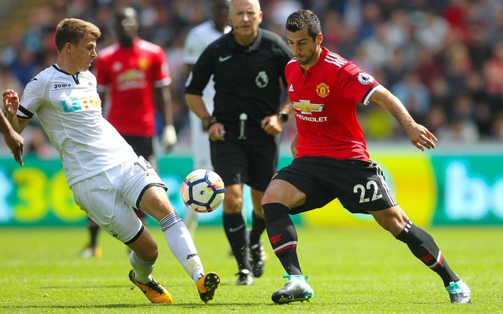 Henrikh Mkhitaryan (R) of Manchester United and Tom Carroll of Swansea City contest possession.