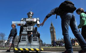 "People look at a mock killer robot in central London at the launch of the ""Campaign to Stop Killer Robots""."