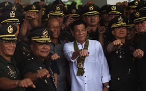 Philippine President Rodrigo Duterte photographed making his trademark raised fist gesture as he meets military officers in Manila, October 2016.