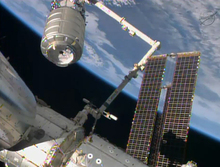 The Cygnus cargo ship (top left) being captured by a robotic arm and brought to the International Space Station on Sunday.