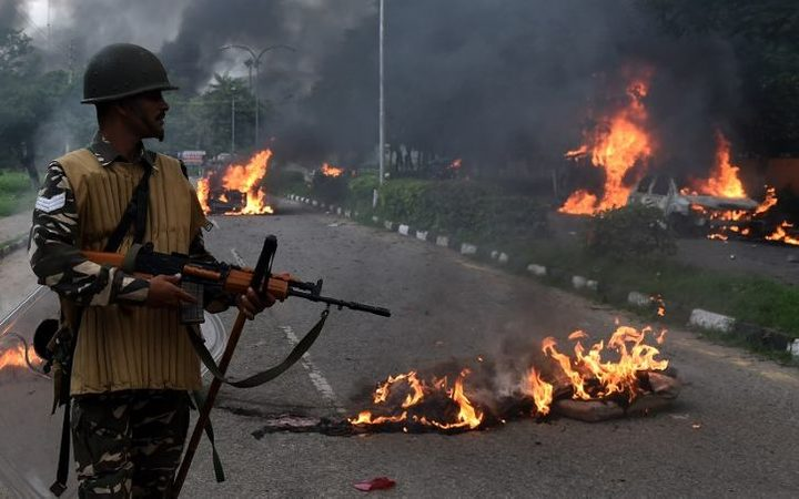 Burning vehicles set alight by rioting followers of a popular religious leader in north India.