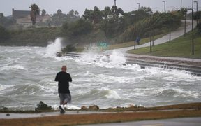 Sal Valerio walks near the bay waters as they churn from approaching Hurricane Harvey.