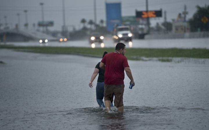 People walk though flooded streets in Houston.