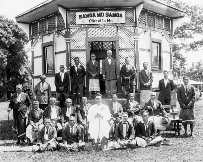 Shows group of men, including Tupua Tamasese Lealofi III (dressed in white), gathered around the office of the Mau ca 1928 with the slogan Samoa Mo Samoa over the door.