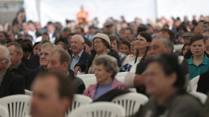 Hundreds of mourners watch the funeral service from the overflow area in a marquee.