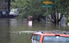 A man waves down a rescue crew as he tries to leave an area of Houston that has been swamped by floodwaters.
