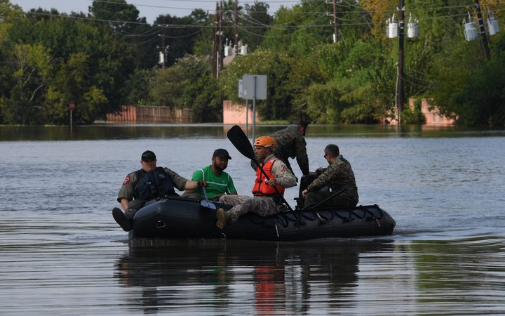 Military and State Troopers help evacuate a man beside the spillway area of the Barker Reservoir in the Coldine area after Hurricane Harvey caused widespread flooding.