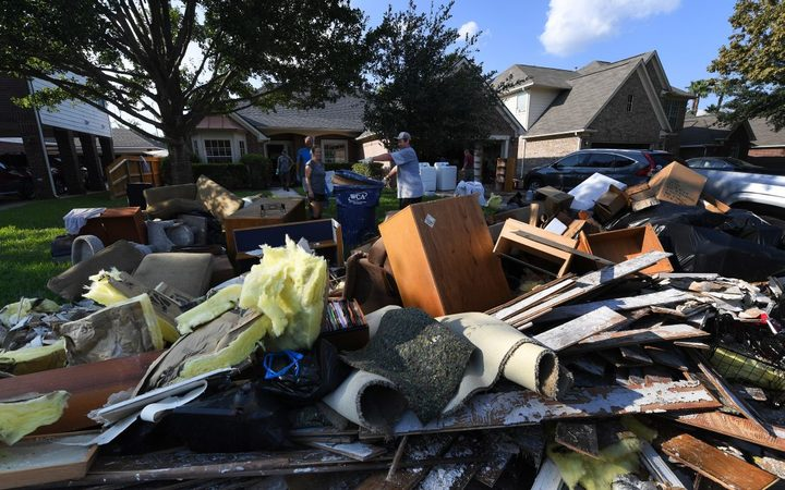 Members of the Olson family remove debris and damaged items from their father's home in the Twin Oaks Estate after flooding caused by Hurricane Harvey.