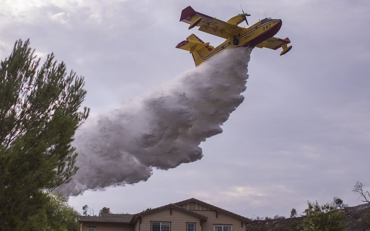 A Super Scooper CL-415 firefighting aircraft makes a drop to protect a house during the La Tuna Fire near Burbank, California.