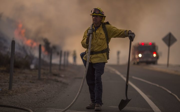 A firefighter holds a hose on the 120 freeway during fight against the La Tuna Fire.