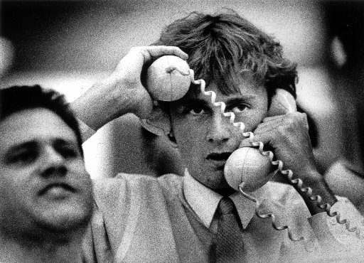 A sharemarket dealer visibly distressed with a telephone held to each ear.