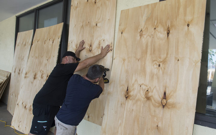 Workers put plywood over the windows at a Publix Supermarket in preparation for Hurricane Irma in Miami, Florida.