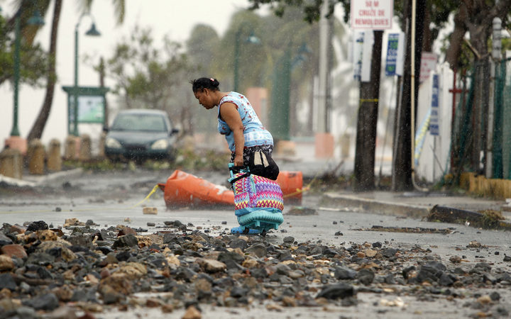 A woman pulls a travel case on a rock scattered road in the aftermath of Hurricane Irma in Fajardo, Puerto Rico.