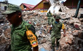 Police and army members search through rubble in Juchitan