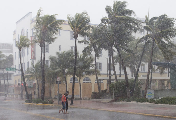 People walk down a Miami Beach  street as winds and rain from Hurridane Irma begin to hit.