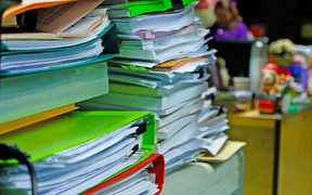 Pile of paperwork in folders on desk (stock image).